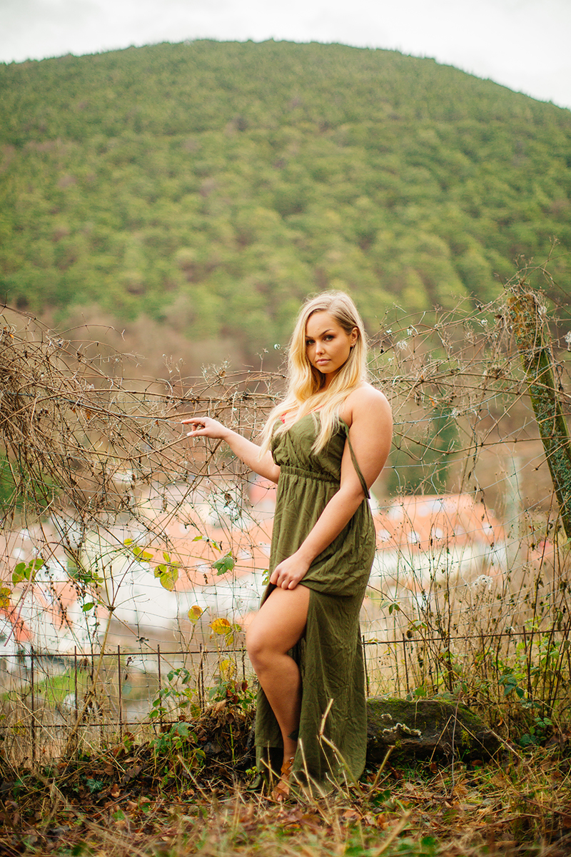 A beautiful young blonde woman wearing a green dress with a village behind her for a Hardenburg Castle boudoir photography session in Bad Dürkheim, Germany