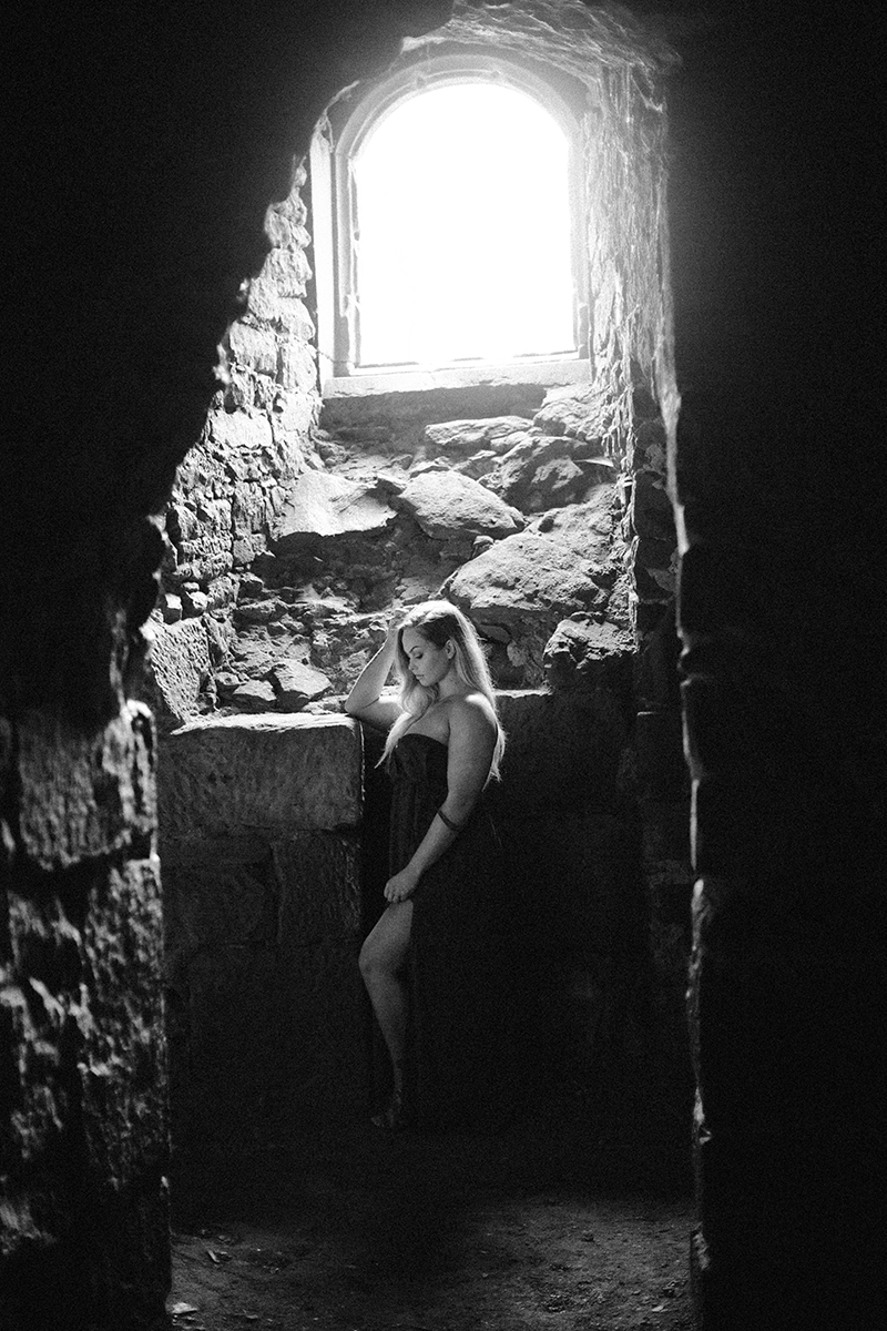 A beautiful young blonde woman wearing a green dress in a tunnel of a castle for a Hardenburg Castle boudoir photography session in Bad Dürkheim, Germany