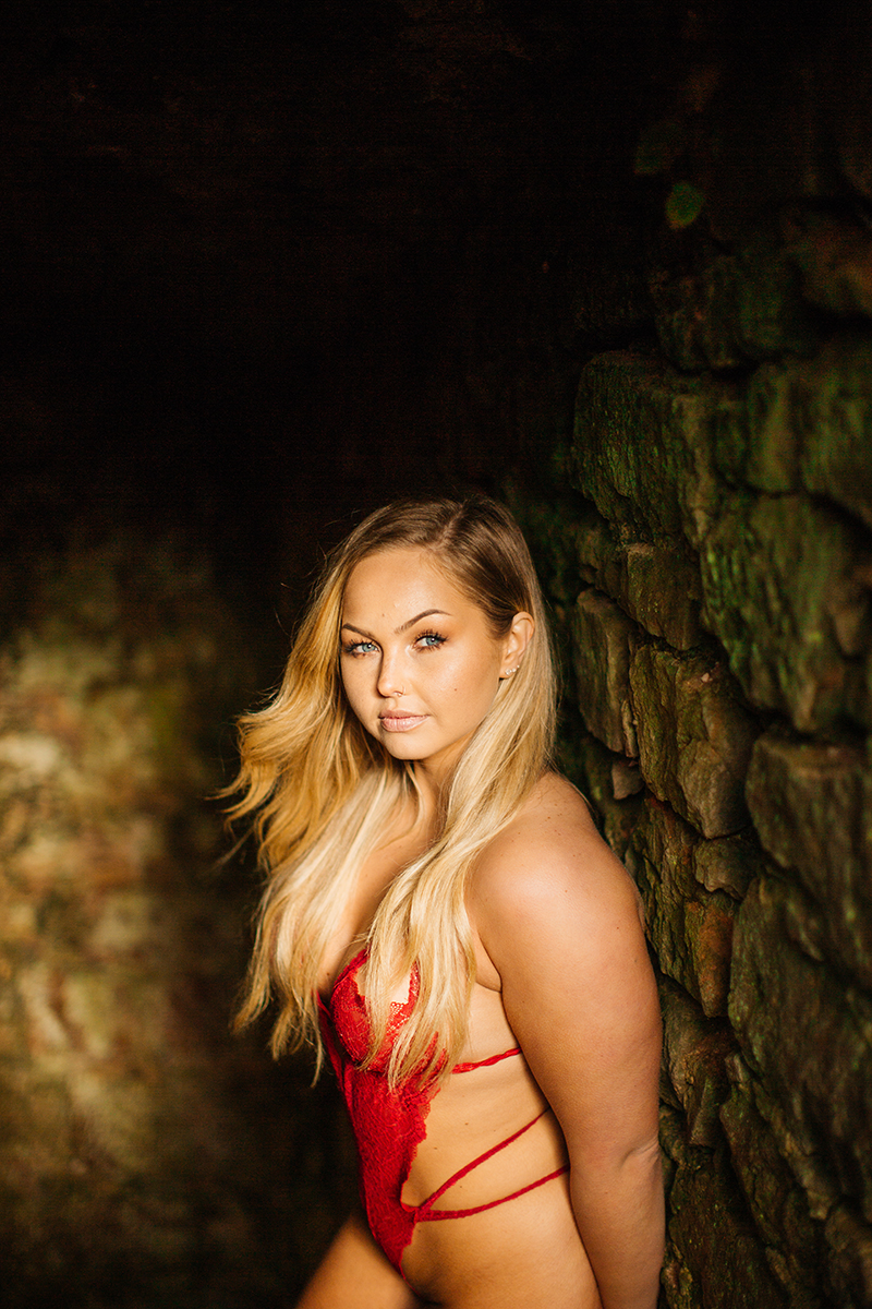 A beautiful young blonde woman wearing red lingerie in a tunnel of a castle for a Hardenburg Castle boudoir photography session in Bad Dürkheim, Germany