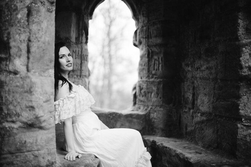 A beautiful brunette woman sitting in a white dress in front of a stone window while it's snowing for a Gräfenstein Castle boudoir photography session in Merzalben near Kaiserslautern, Germany