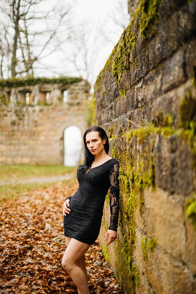 A beautiful brunette woman leaning in a black dress against a stone wall while it's raining for a Gräfenstein Castle boudoir photography session in Merzalben near Kaiserslautern, Germany