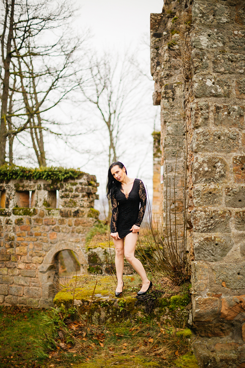 A beautiful brunette woman posing in a black dress in the rain for a Gräfenstein Castle boudoir photography session in Merzalben near Kaiserslautern, Germany