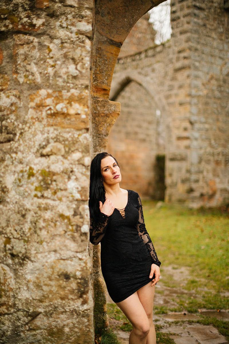 A beautiful brunette woman posing in a black dress leaning against a stone wall in the rain for a Gräfenstein Castle boudoir photography session in Merzalben near Kaiserslautern, Germany