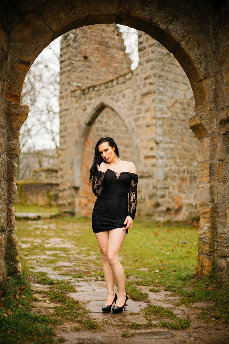 A beautiful brunette woman posing in a black dress in a stone arch in the rain for a Gräfenstein Castle boudoir photography session in Merzalben near Kaiserslautern, Germany