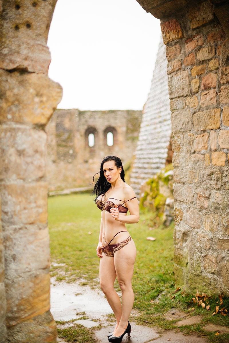 A beautiful brunette woman posing in a bra and underwear in a stone arch in the rain for a Gräfenstein Castle boudoir photography session in Merzalben near Kaiserslautern, Germany