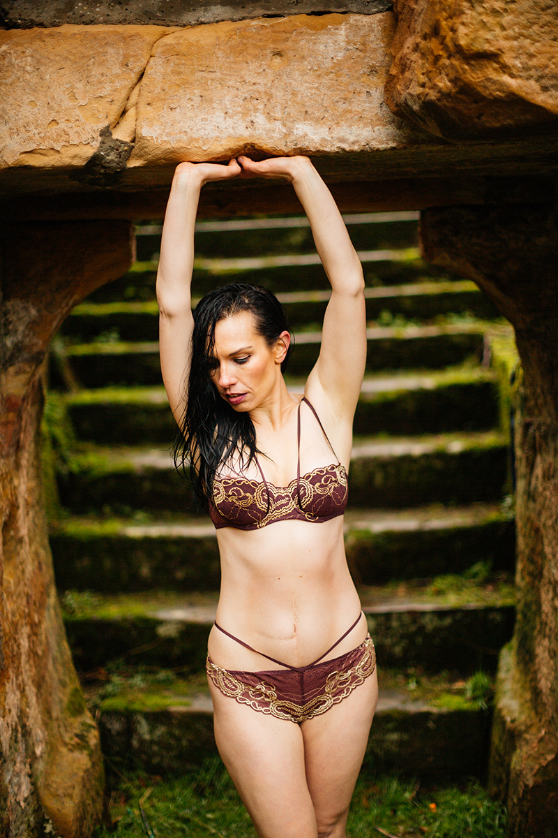 A beautiful brunette woman posing in a bra and underwear in a stone arch in front of stairs in the rain for a Gräfenstein Castle boudoir photography session in Merzalben near Kaiserslautern, Germany
