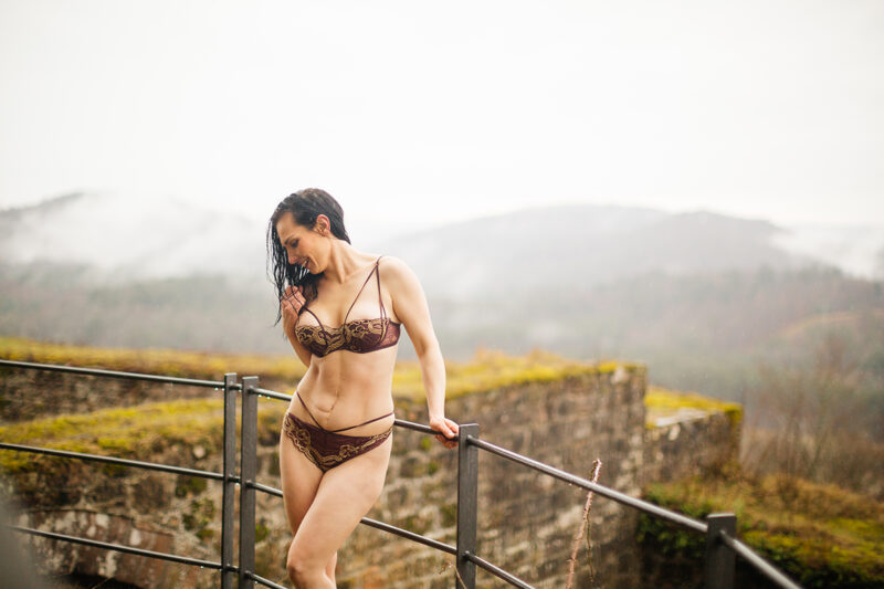 A beautiful brunette woman posing in a bra and underwear in the rain with mountains behind for a Gräfenstein Castle boudoir photography session in Merzalben near Kaiserslautern, Germany