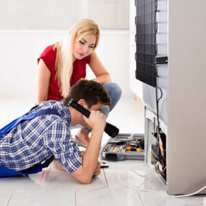 Woman Looking At Male Worker Repairing Refrigerator In Kitchen Room