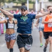 Runner excitedly crosses the 2019 Austin Half Marathon finish line. Run Austin, the #1 city in America and you will understand why people love the Austin Marathon!