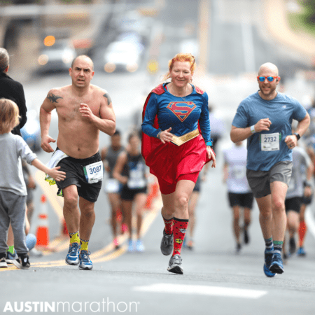 Man runs up hill during austin marathon with a spectator dressed as wonder woman cheering them on