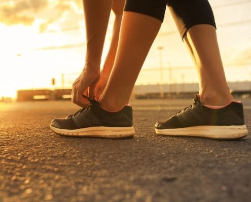 Runner ties shoes before going on a morning run.