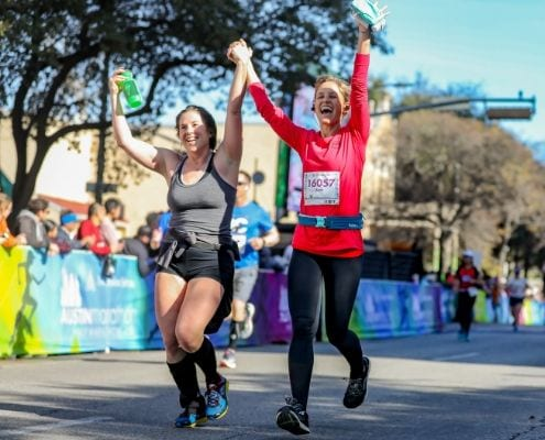 Friend crossing the Austin Half Marathon finish line together; accountability is a great tip to stay motivated.