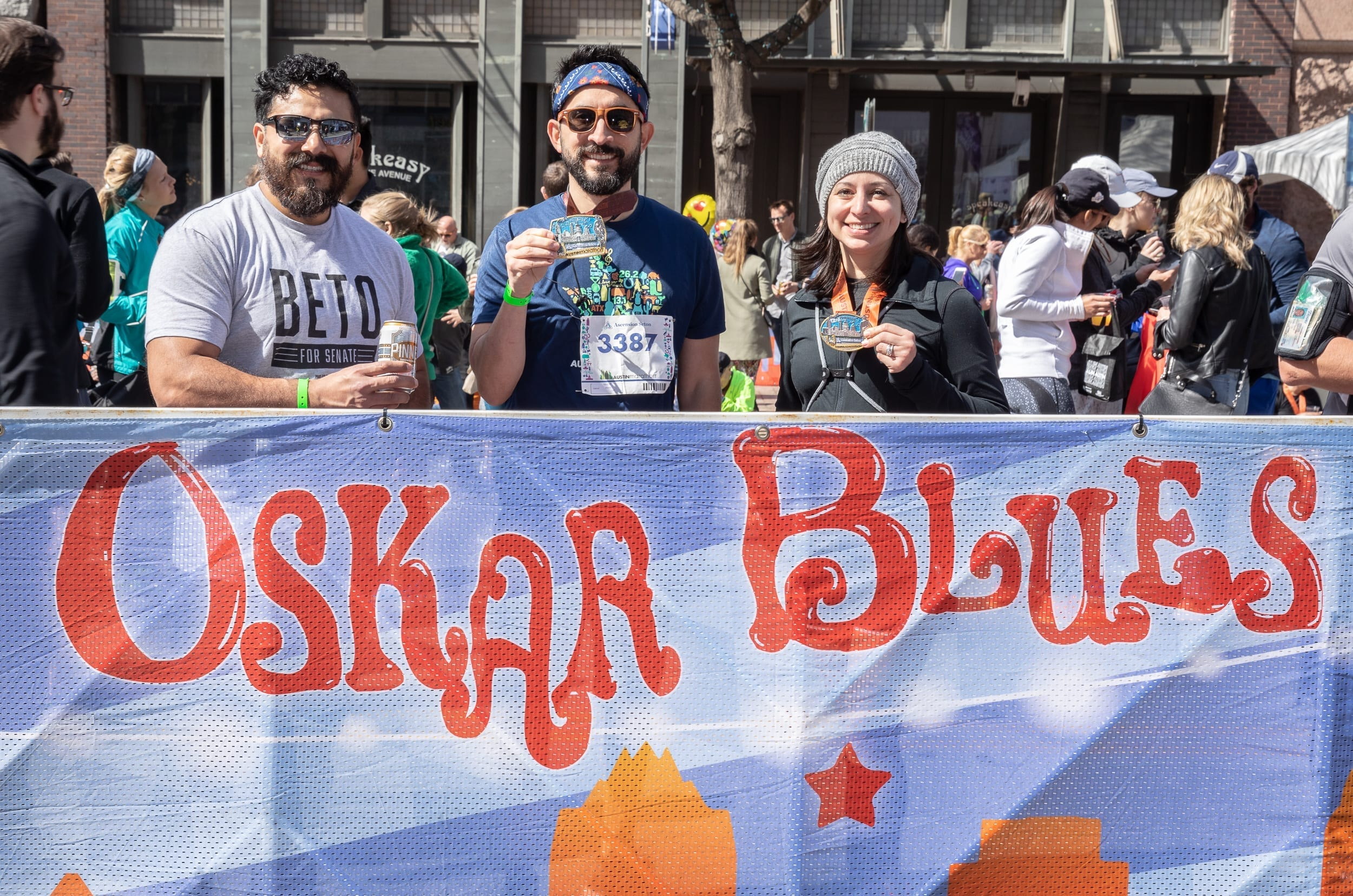 Runners show off their Austin Marathon finisher medals at the Oskar Blues Austin beer garden in the Austin Marathon's 3-block-long finish line festival.