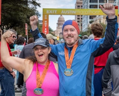 Two runners celebrate after crossing the 2019 Austin Half Marathon finish line.