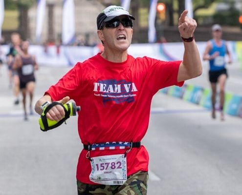 Runner crosses 2019 Austin Half Marathon finish line wearing an American flag SPIbelt. SPIbelt returns as the Official Race Belt of the 2020 Ascension Seton Austin Marathon.