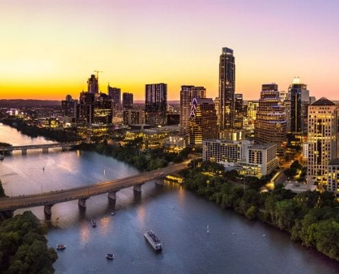 Drone image of downtown Austin and the sunset. Runners can get a good night's sleep and stay near the Austin Marathon start and finish lines when they book their downtown Austin hotel with with the Hotels for Hope booking platform.
