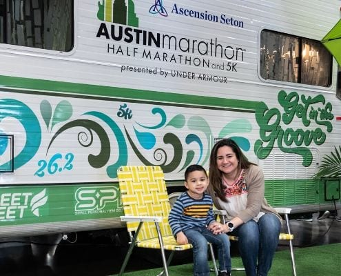 Image of mother and son in front of the Austin Marathon Winnebago at the 2019 Austin Marathon expo. Winnie is returning and will be a 2020 expo highlight.