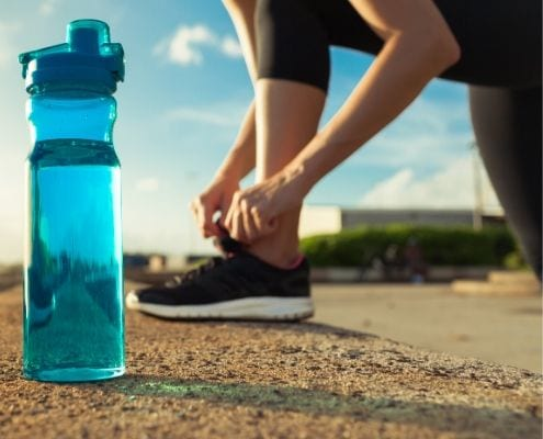 Image of runner tying her shoe with a water bottle nearby. Christy Thomas began running because she wanted to make a lifestyle change. She will run the 2020 Austin Half Marathon!