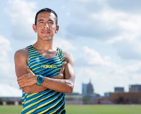 Leo Manzano, Austin Marathon Race Ambassador and Olympic silver medalist, poses on the University of Texas track with downtown Austin in the background. Manzano takes you back to his first sub-four-minute mile in this blog post.