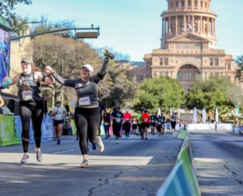 Two female participants cross the 2019 Austin Half Marathon finish line while their arms are raised in excitement. Follow these 4 taper tips to ensure you have a similar experience at the 2020 Ascension Seton Austin Marathon.