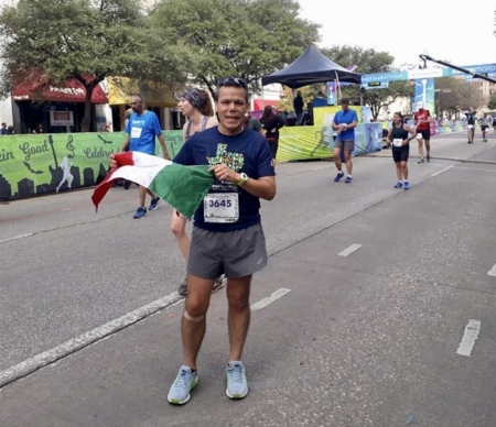 Jose Antonio Santiago poses at the 2019 Austin Marathon finish line with a Mexican flag. His life-changing journey began when he started running nine years ago.