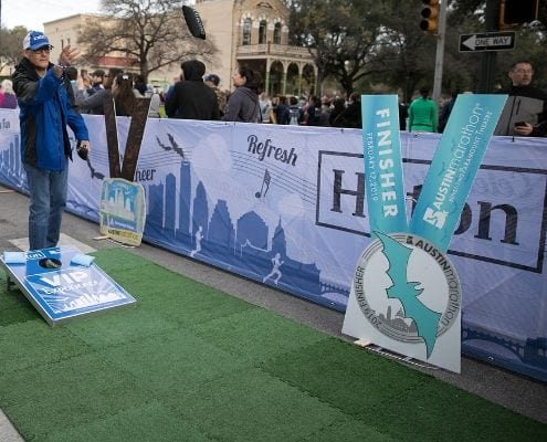 Image of participant playing bag toss at the 2019 Austin Marathon Hilton VIP Experience. Hilton is the 2020 Austin Marathon's Preferred Hotel Partner.