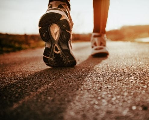 Image of runner walking on concrete on their life-changing journey.