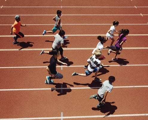 Image of children running on the track during a Marathon Kids event. Marathon Kids is the beneficiary of the Manzano Mile presented by Dole Packaged Foods.