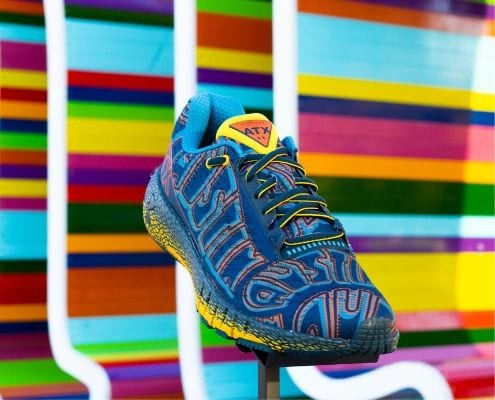 Image of the limited-edition Under Armour HOVR Machina ATX shoe in front of a multi-colored ATX sign. The Austin Marathon is giving away a pair of these shoes every day in April for their 30th Anniversary Giveaway! Credit: Fleet Feet Austin.
