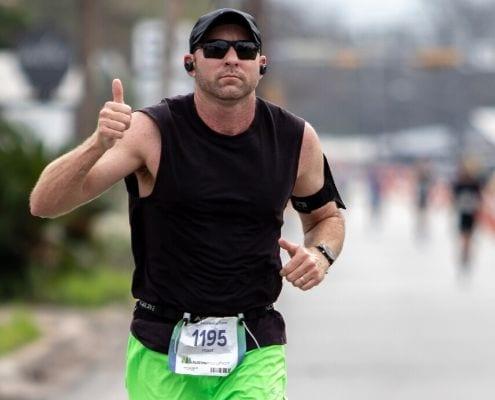 Image of runner giving the thumbs up while listening to music during the 2020 Austin Marathon. Read this blog and listen to the 10 most recent March running playlist additions.