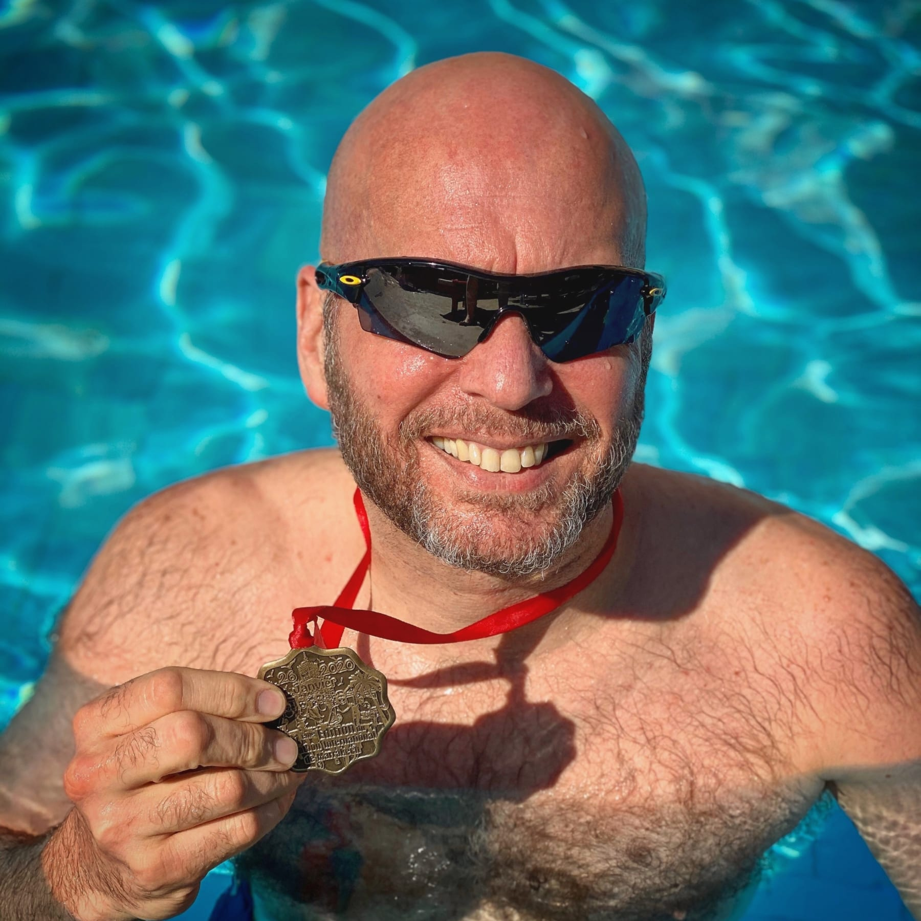 Image of Jonathan Acott in a pool showing off his medal from the Marrakesh Marathon. Read about his journey to run the world and how the Austin Marathon is next!