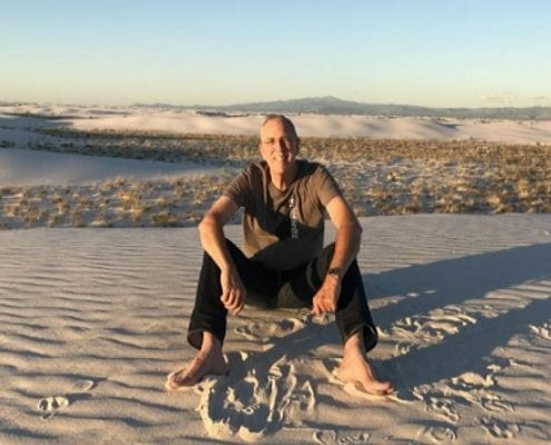 Image of Joe Priesnitz sitting on a sand dune. Joe booked live music acts for the Austin Marathon and 3M Half Marathon before his passing on April 25, 2020. Courtesy of Barbara Nadalini Priesnitz.