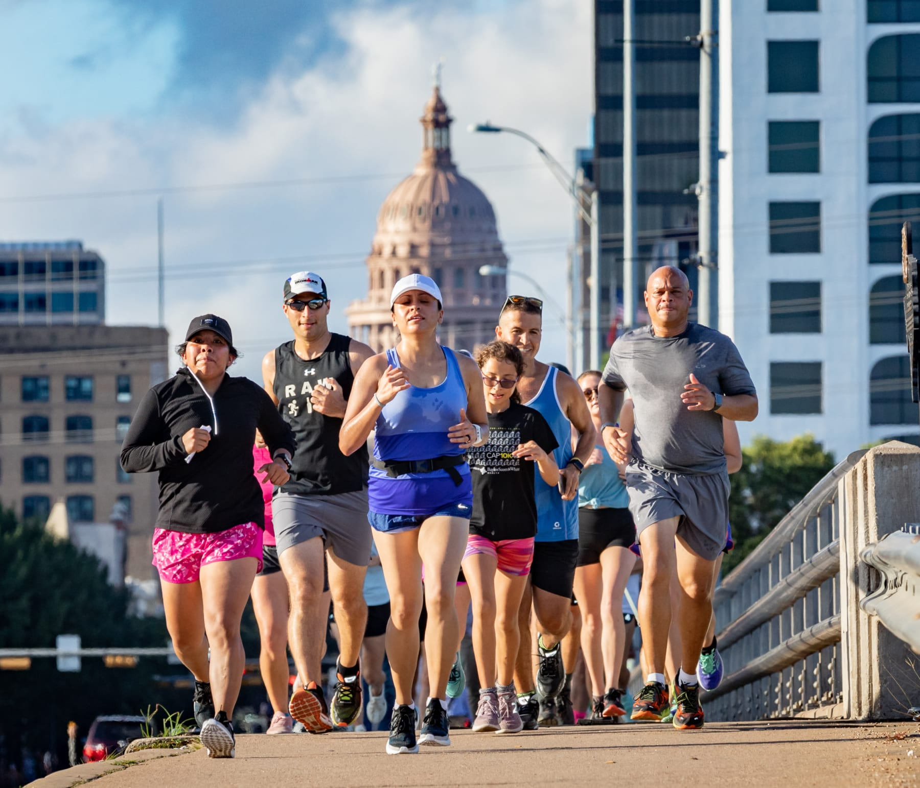 Image of runners running during the 2019 free Global Running Day event on the Congress Avenue Bridge in Austin with the Texas State Capitol in the background.