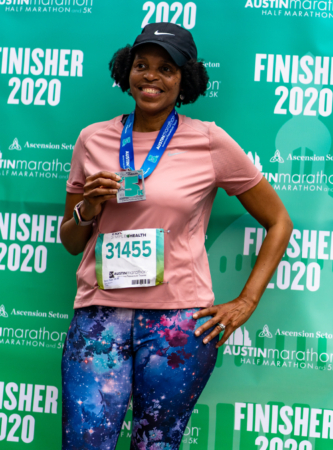 Image of a runner posing in front of a 2020 Finisher backdrop after completing the 2020 KXAN Simple Health 5K. First-time runners should set a goal and find a corresponding training plan, like the free 5K training plan in this blog.
