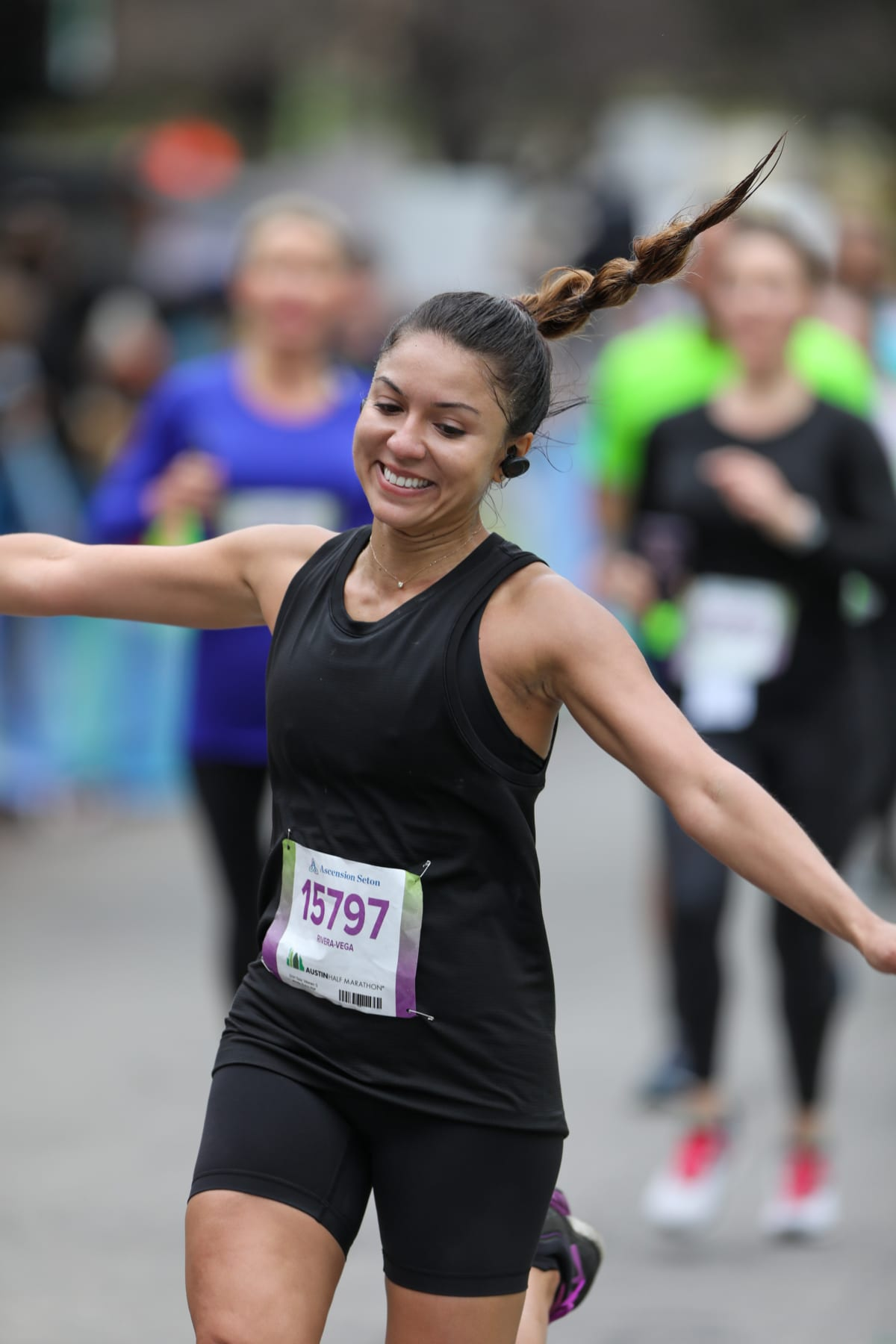 Image of female runner smiling with her arms outstretched, crossing the 2020 Austin Half Marathon finish line. Read the advice in this blog and learn how to increase your mileage.