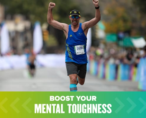 Runner crosses the Austin Marathon finish line with both arms raised triumphantly. Text on design reads Build Your Mental Toughness. Learn more at https://youraustinmarathon.com/build-mental-toughness/