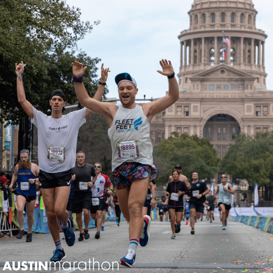 Two runners jump for joy with their hands raised in the air as they cross the 2020 Austin Half Marathon finish line.