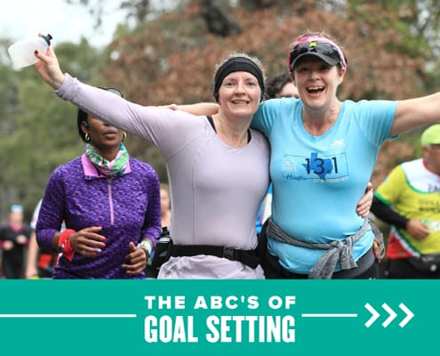 Two women happily stand side-by-side with their arms in the air during the 2020 Ascension Seton Austin Marathon. Text on design reads The ABCs of Goal Setting. Learn more at https://youraustinmarathon.com/goal-setting/