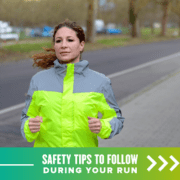 Female runner runs on the road against traffic wearing a bright yellow high-visibility jacket. Text on design reads Safety Tips to Follow During Your Run. Read more at https://youraustinmarathon.com/running-safety-tips/