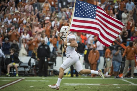 Nate Boyer carries the American flag for the Texas Longhorns before a home game. Courtesy of Nate Boyer.