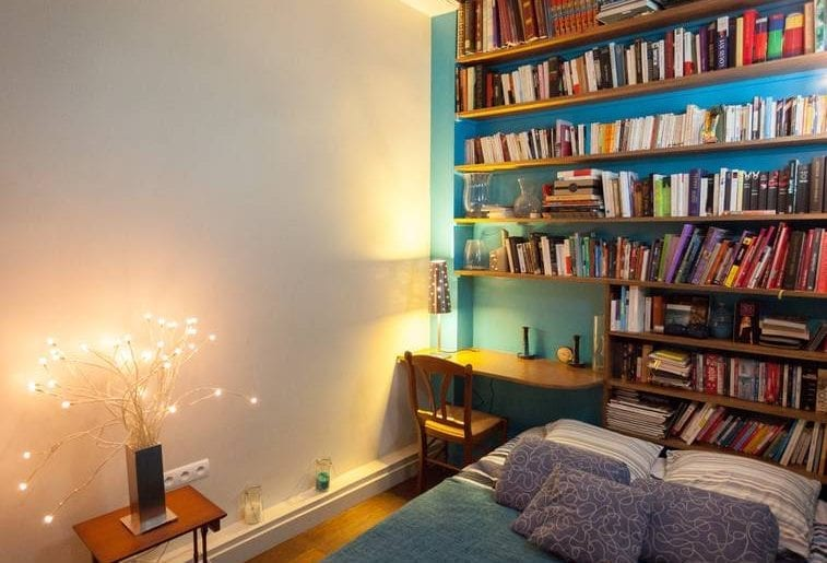 Cozy bedroom with extensive bookshelf