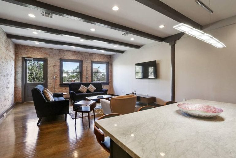 The open floor plan accents the exposed brick wall and bright windows of the private balcony.