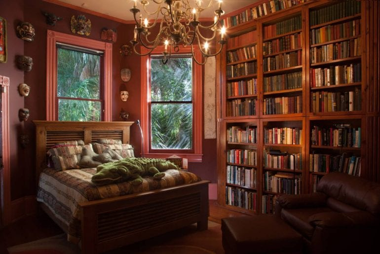 Floor to ceiling bookshelves fill this gorgeous bedroom along with unique artifacts and art