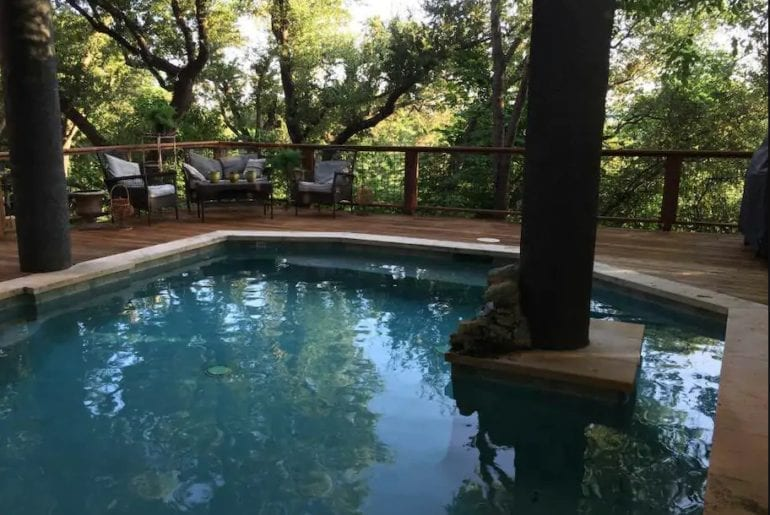 This outdoor space is complete with patio furniture and a beautiful private pool