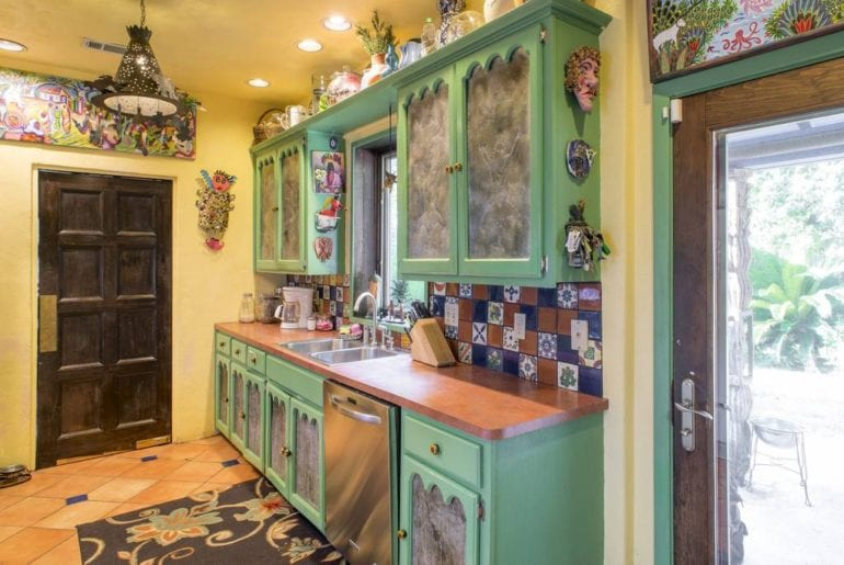 This bright kitchen has wonderfully vibrant tiling and handmade cabinet doors