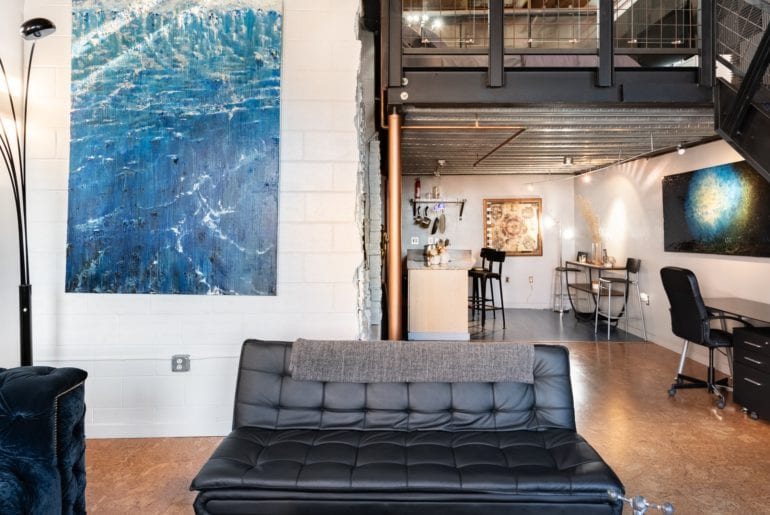 The interior design includes modern art pieces, leather couches, and exposed piping