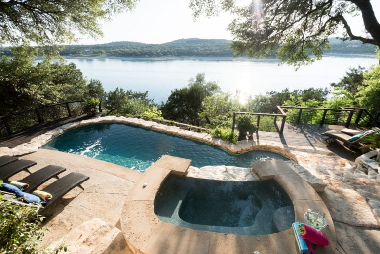 The backyard boasts breathtaking views of Lake Travis from the saltwater pool and hot tub