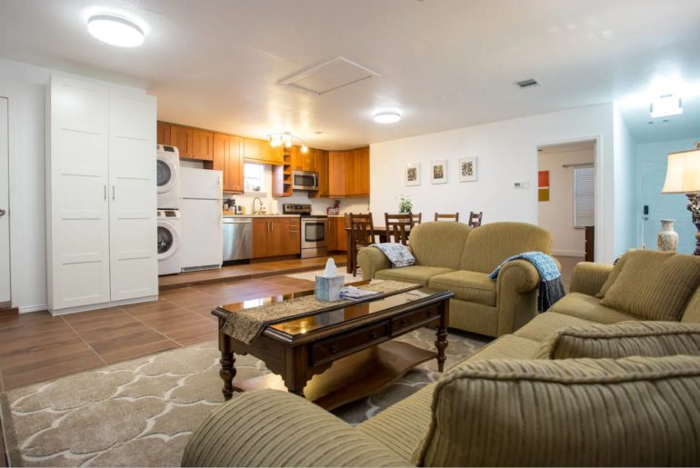 There is a spacious living area with a cozy sofa, gourmet kitchen, and a cute dining area