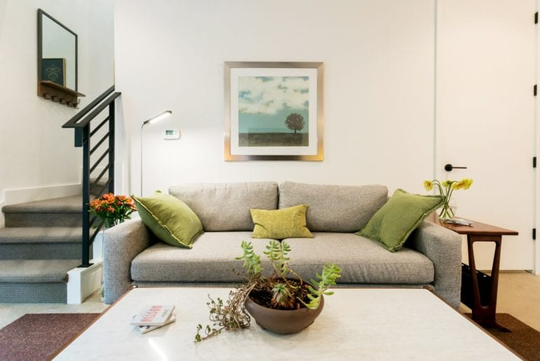 The guesthouse is complete with fresh flowers, a cozy couch and green accent pillows. Austin Hilton