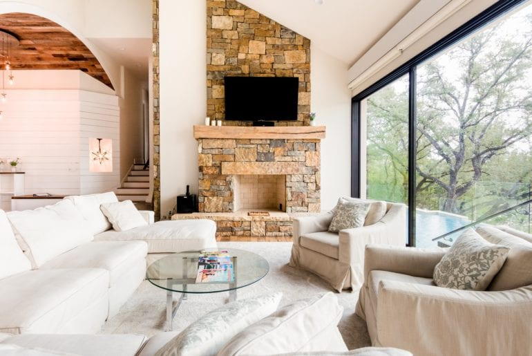 The living room has a stone fireplace, with enormous sliding glass doors and cozy white sofas.